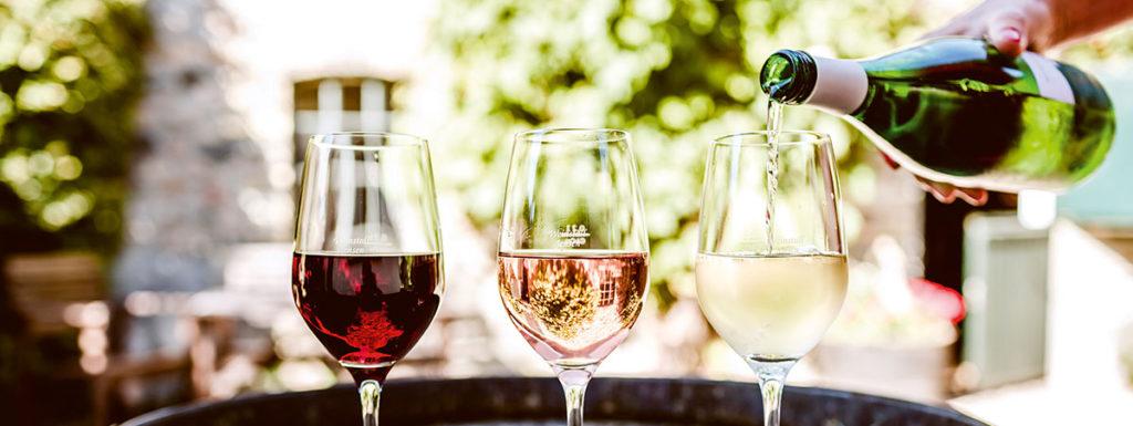 3 Weingläser auf einem Weinfass